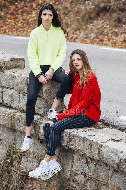 Young attractive stylish friends in bright knitted sweaters sitting on stones near route — Stock Photo