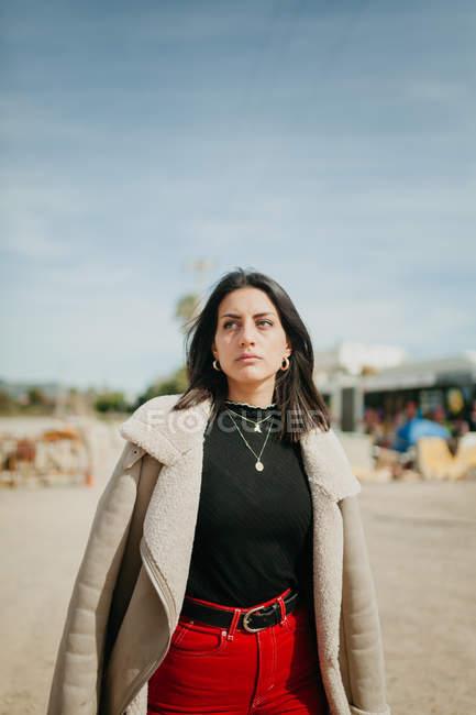 Bella sognante giovane donna in abito alla moda con giacca in piedi su sfondo sfocato della spiaggia — Foto stock