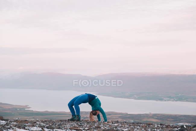 Вид сбоку на женщину, склоняющуюся назад на холме у реки — стоковое фото