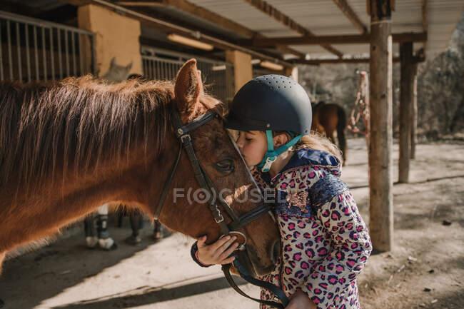 Menina bonito no capacete beijando um cavalo branco enquanto está perto de barracas no estábulo durante a aula de equitação no rancho — Fotografia de Stock