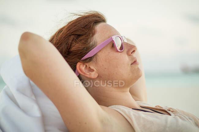 Hermosa hembra en tonos de moda mirando hacia otro lado mientras está acostada en una bolsa de frijoles blandos en un día soleado en Maldivas - foto de stock
