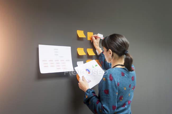 Підприємець тримає документ і писати на липких нотаток, стоячи біля сірої стіни в офісі — стокове фото