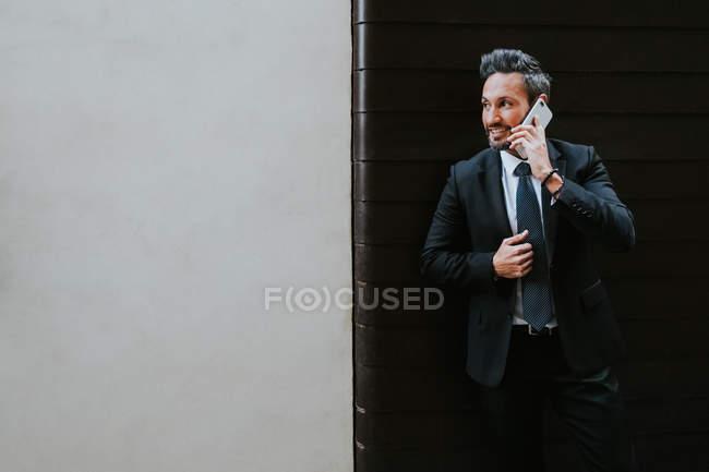 Взрослый красивый элегантный бизнесмен в формальном костюме смотрит в сторону и разговаривает по мобильному телефону у стены — стоковое фото