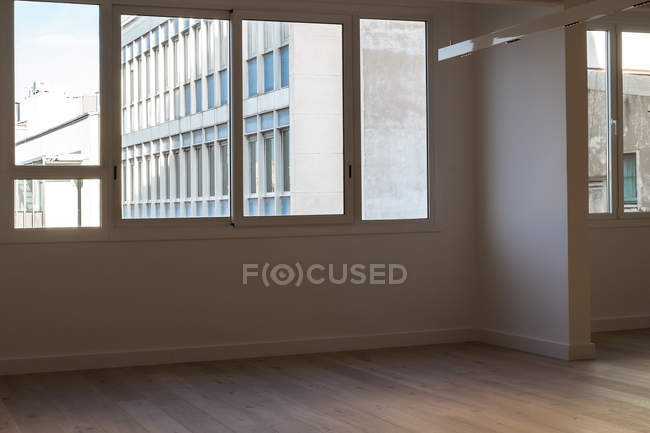 Windows and white walls inside spacious empty room of modern apartment - foto de stock