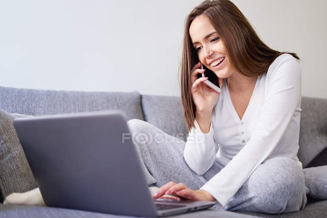 Smiling young happy woman using laptop and talking on mobile phone on sofa at home — Stockfoto