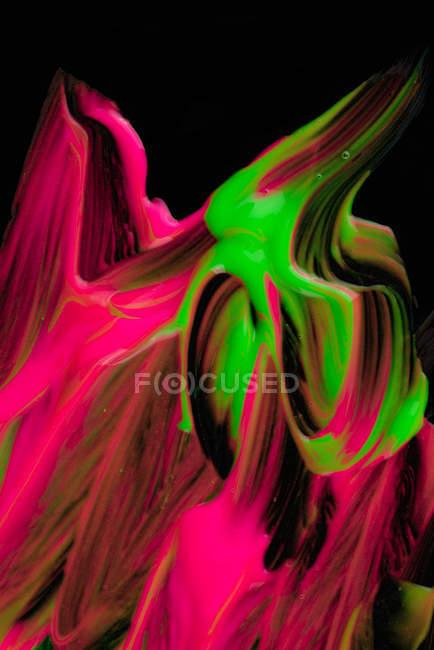 Déversements de pigment épais de différentes couleurs mélangeant sur fond noir — Photo de stock