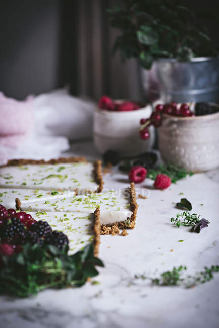 Pieces of homemade lime pie with berries on white marble surface — Stock Photo