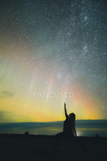 Silhouette of woman with upped hand doing yoga on land near amazing north lights in sky with many stars at night — Stock Photo