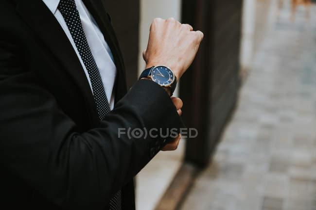 Abgeschnittenes Bild eines Geschäftsmannes im formellen Anzug, der Uhr auf verschwommenem Hintergrund zeigt — Stockfoto