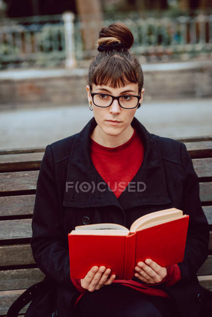 Young elegant woman in eyeglasses reading book and sitting on bench in city park — Stock Photo