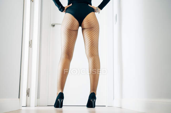 Back view of provocative female with perfect buttocks wearing erotic bodysuit and fishnet tights and posing — Stock Photo