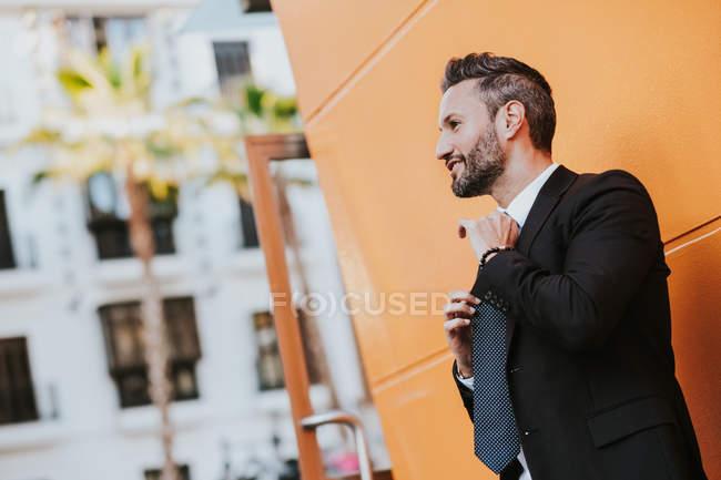 Взрослый красивый элегантный бизнесмен в формальном костюме, поправляя галстук и отводя взгляд от оранжевой стены — стоковое фото