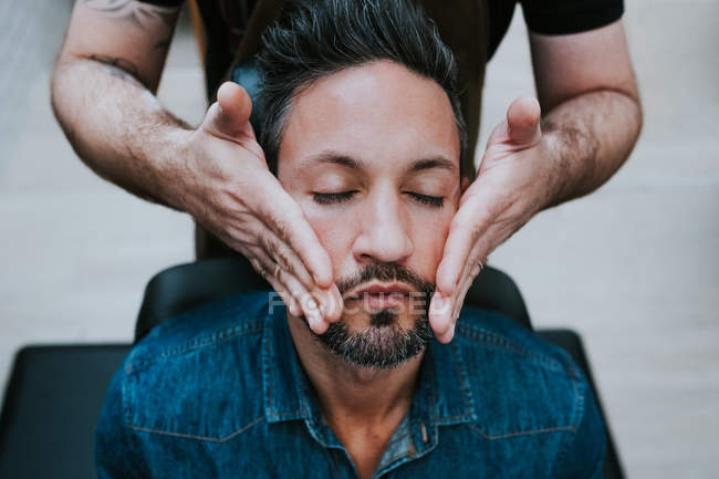Barber doing face massage to handsome stylish male with closed eyes sitting in chair — Stock Photo