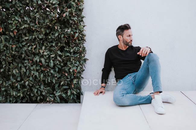 Adulto bello elegante uomo pensoso in abbigliamento casual seduto sul pavimento e guardando lontano vicino alla parete grigia — Foto stock