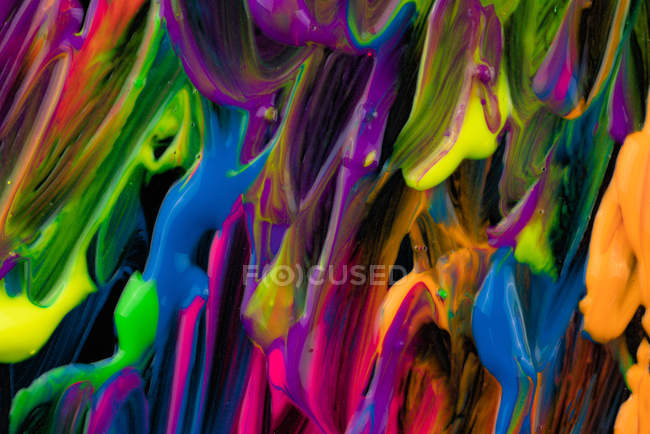 Spills of thick pigment of various colors mixing on black background — стоковое фото