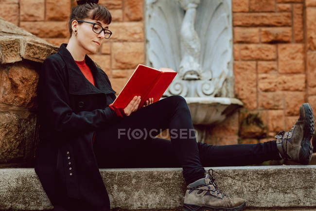 Young elegant woman in eyeglasses reading book and sitting on stairs — Stock Photo