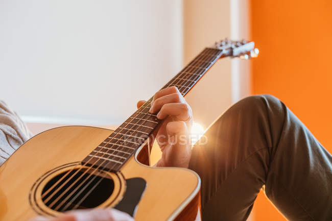 Hand of man playing guitar in room — Stock Photo