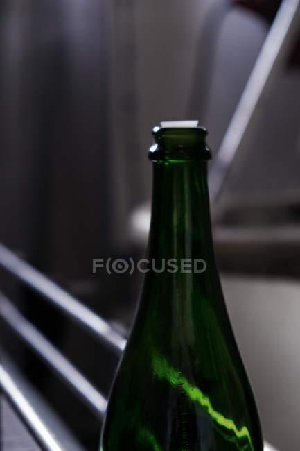 Garrafa de vinho verde selada movendo-se na correia transportadora moderna na adega — Fotografia de Stock