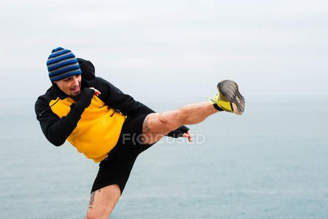 Дорослий бородатий людина в спортивному одязі практикуючих кікбоксингу тренування на морському узбережжі — стокове фото