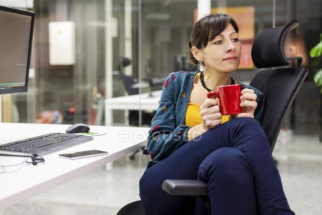 Продуманий жіночий менеджер з кухлем гарячого напою відпочиває на кріслі в офісі — стокове фото