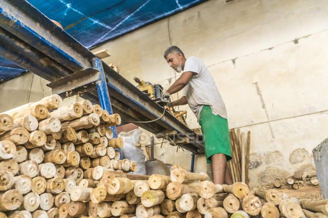 Homme utilisant une machine à bois en atelier avec un tas de bâtons de bois — Photo de stock