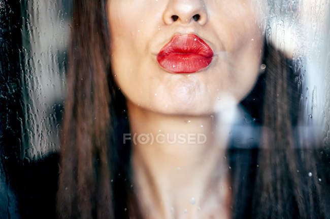 Closeup of female red lips kissing clean transparent glass passionately — Stock Photo