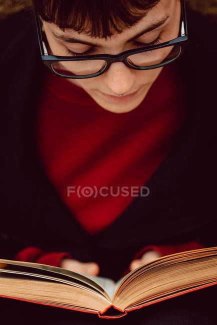 Close-up of young elegant woman in eyeglasses reading book — Stock Photo