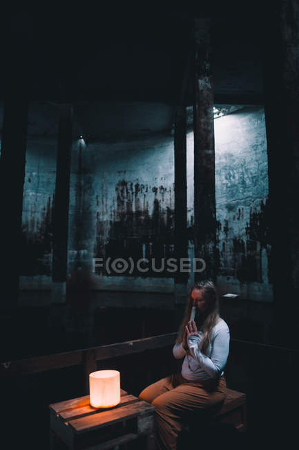 Young woman with praying hands sitting near lights in dark building — Stock Photo