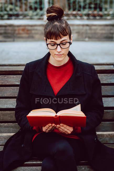Молода елегантна жінка в окулярах читає книжку і сидить на лавці в городі. — стокове фото