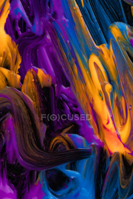 Spills of thick pigment of various colors mixing on black background — Fotografia de Stock