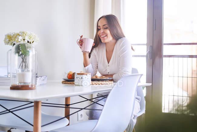 Sorridente giovane donna che fa colazione a tavola vicino alla finestra di casa — Foto stock