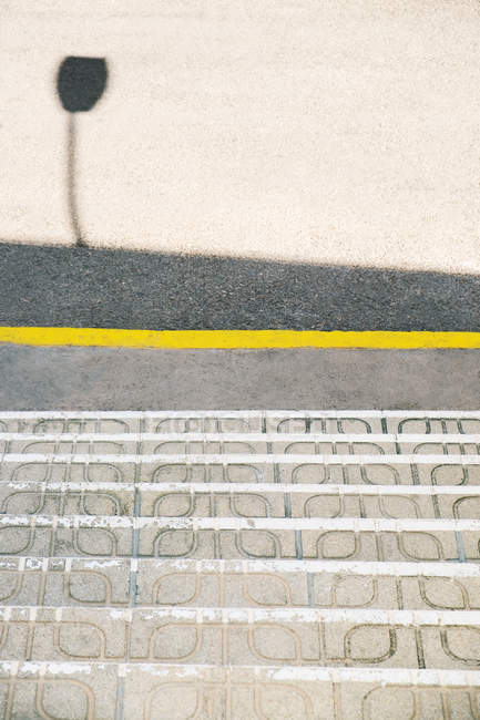 From above shabby stairs and shadow on asphalt road on sunny day on city street — Stock Photo