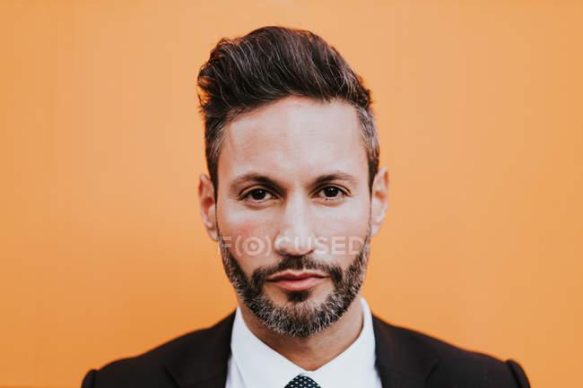 Adult handsome elegant businessman in formal suit looking at camera near orange wall — Stock Photo