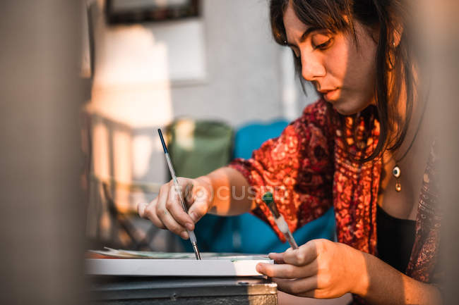 Woman painting on terrace — Stock Photo