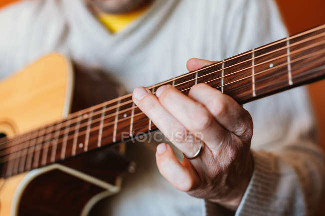 Close-up of man playing guitar on orange background — Stock Photo