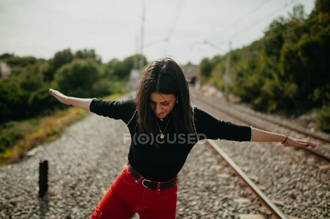 Jeune femme gaie dans la tenue élégante ayant l'amusement tout en restant sur le fond brouillé des rails — Photo de stock