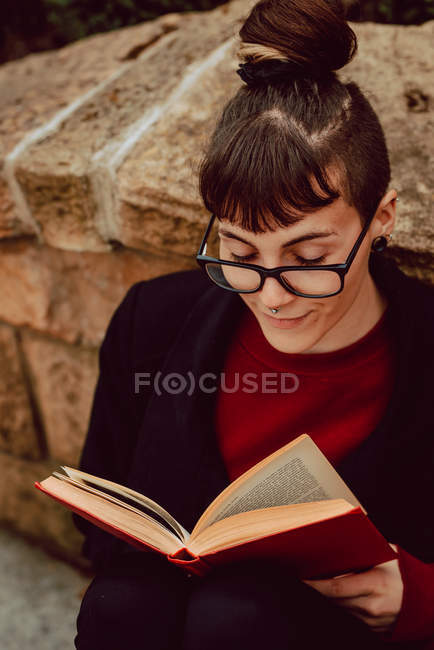 Young elegant woman in eyeglasses leaning on stone wall and reading book — Stock Photo