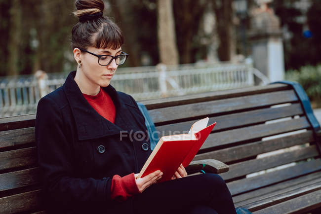 Young elegant woman in eyeglasses reading book while sitting on bench in city park — Stock Photo