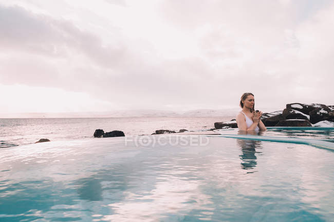 Young woman with closed eyes meditating in water of pool near rocks and cloudy sky — Foto stock