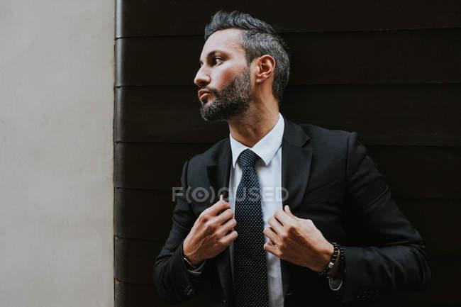 Взрослый красивый элегантный бизнесмен в формальном костюме, корректирующий пиджак и отводящий взгляд у серой стены — стоковое фото