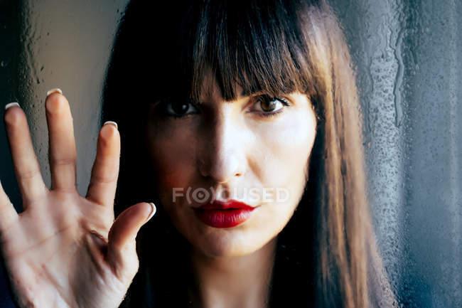Nahaufnahme einer sinnlichen Frau mit roten Lippen, die transparentes Glas berühren — Stockfoto
