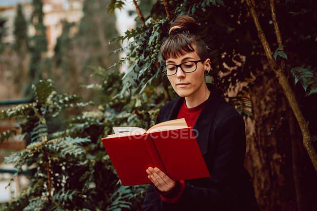 Junge attraktive elegante Frau mit Brille liest Buch im Stadtgarten — Stockfoto