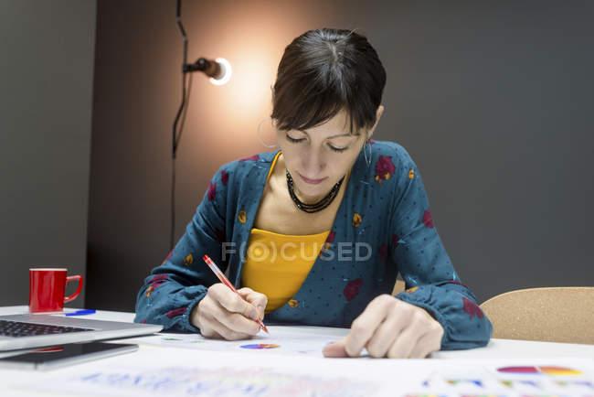 Ділова жінка робить нотатки з графіків, сидячи на столі в сучасному офісі — стокове фото