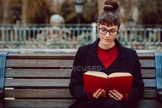 Молодая привлекательная элегантная женщина в очках читает книгу и сидит на скамейке в городском саду — стоковое фото