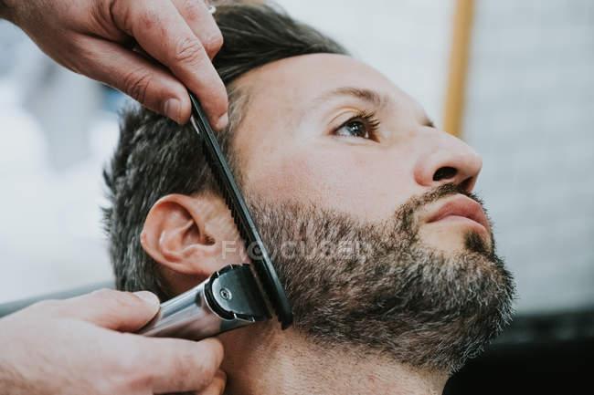 Крупный план парикмахера с расческой и стрижкой бороды мужчины, сидящего в парикмахерской на размытом фоне — стоковое фото