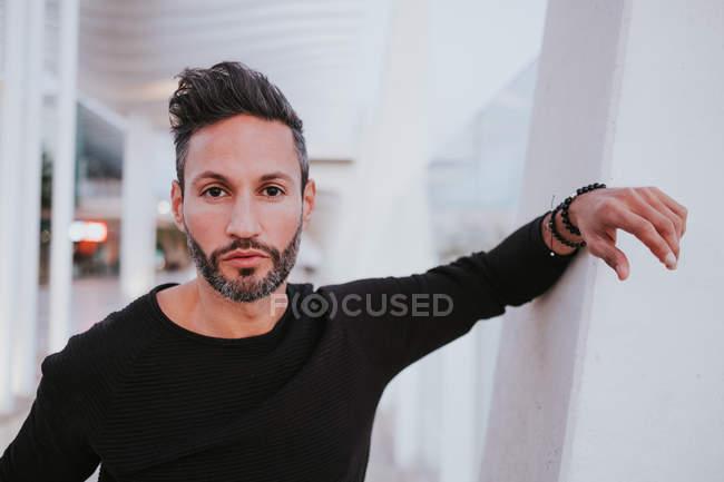 Adulto bello elegante maschio allegro in abbigliamento casual appoggiato sul muro grigio e guardando lontano sulla strada della città — Foto stock