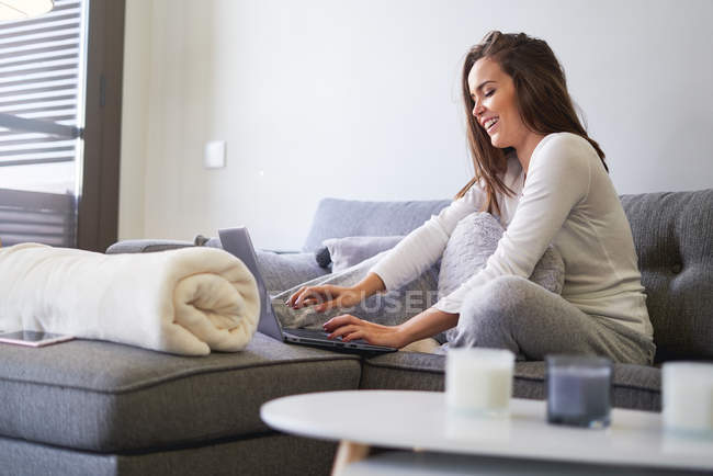 Cheerful young woman using laptop and resting on sofa at home — Stockfoto