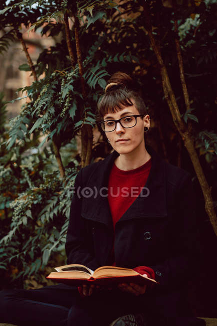 Young elegant woman in eyeglasses sitting with book on bench in city garden — Stock Photo