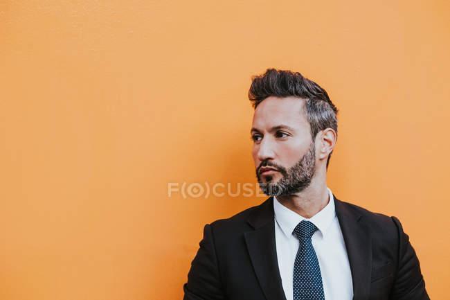 Взрослый красивый элегантный бизнесмен в формальном костюме, корректирующий пиджак и отводящий взгляд у оранжевой стены — стоковое фото