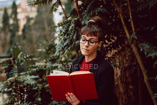 Молодая привлекательная элегантная женщина в очках читает книгу в городском саду — стоковое фото
